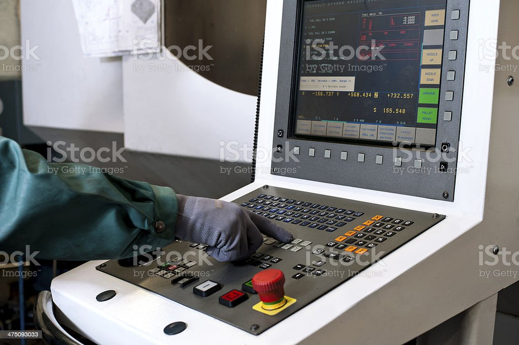 Hand on the control panel of a cnc programmable machine stock photo