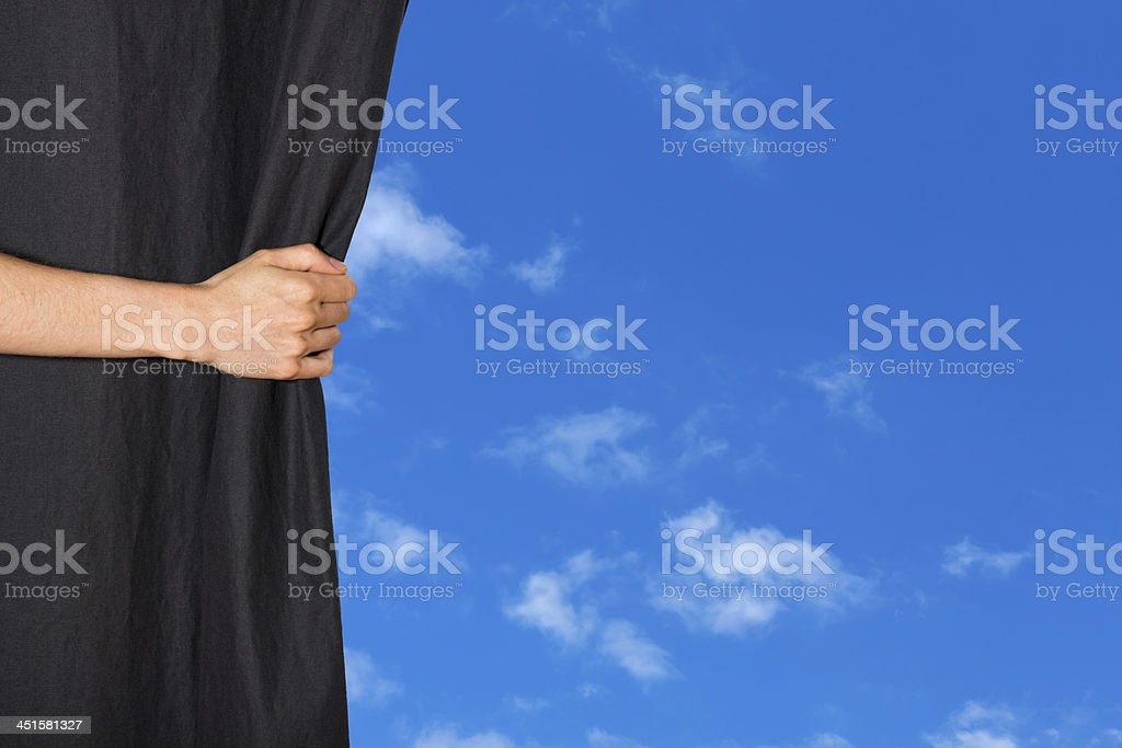 Hand opening a curtain with blue sky behind it stock photo