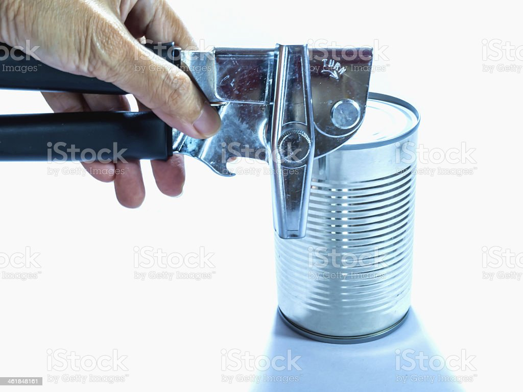 Hand opening a cylindrical can on white background stock photo