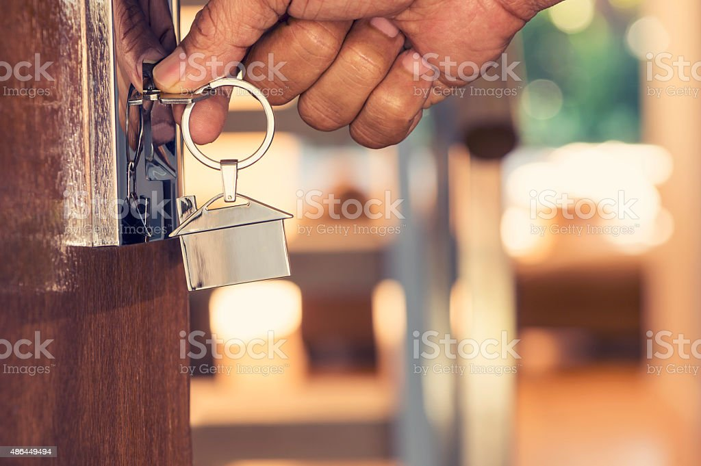 Hand opening a door with a key. stock photo