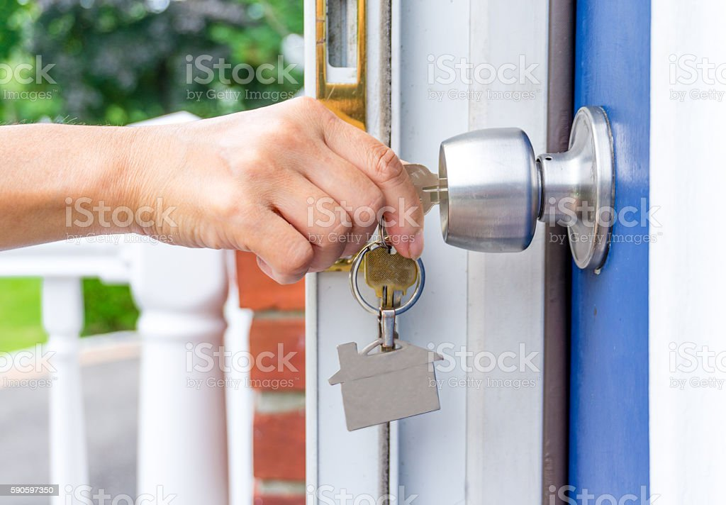 hand opening a door with keys stock photo