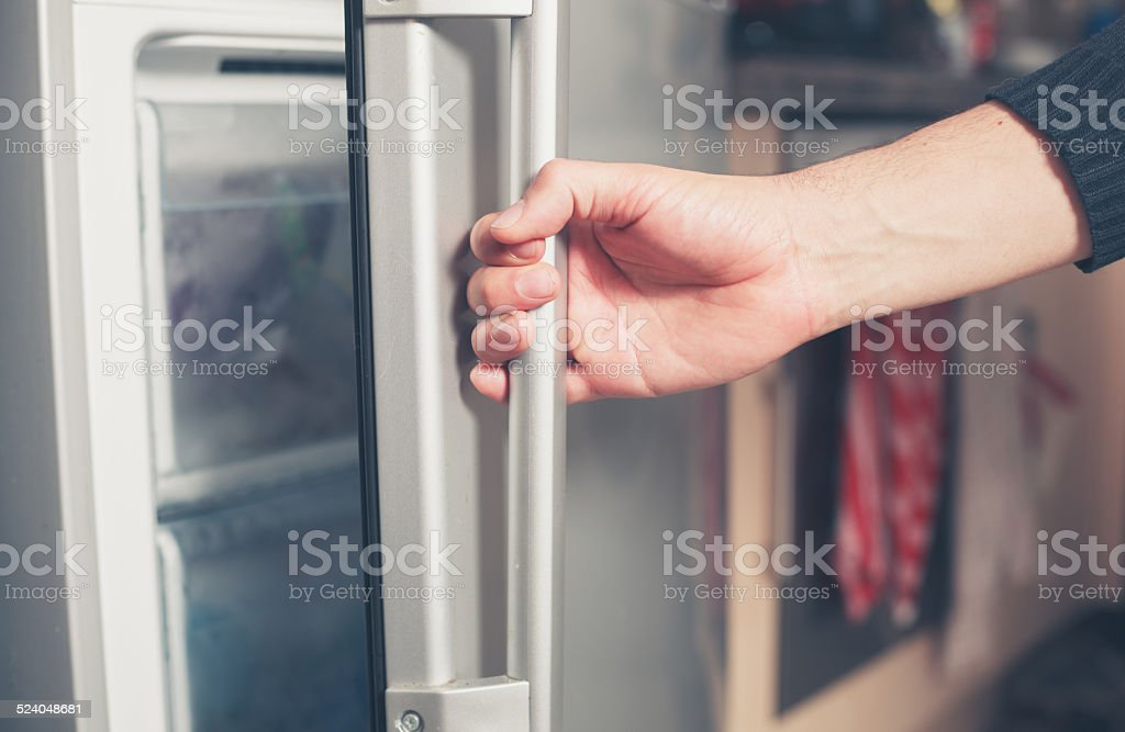 Hand opening freezer door stock photo