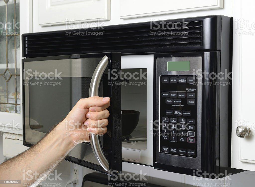 Hand Opening Microwave stock photo