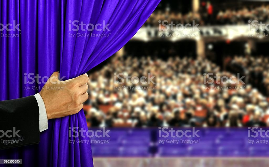 Hand opening stage curtain and audiance stock photo