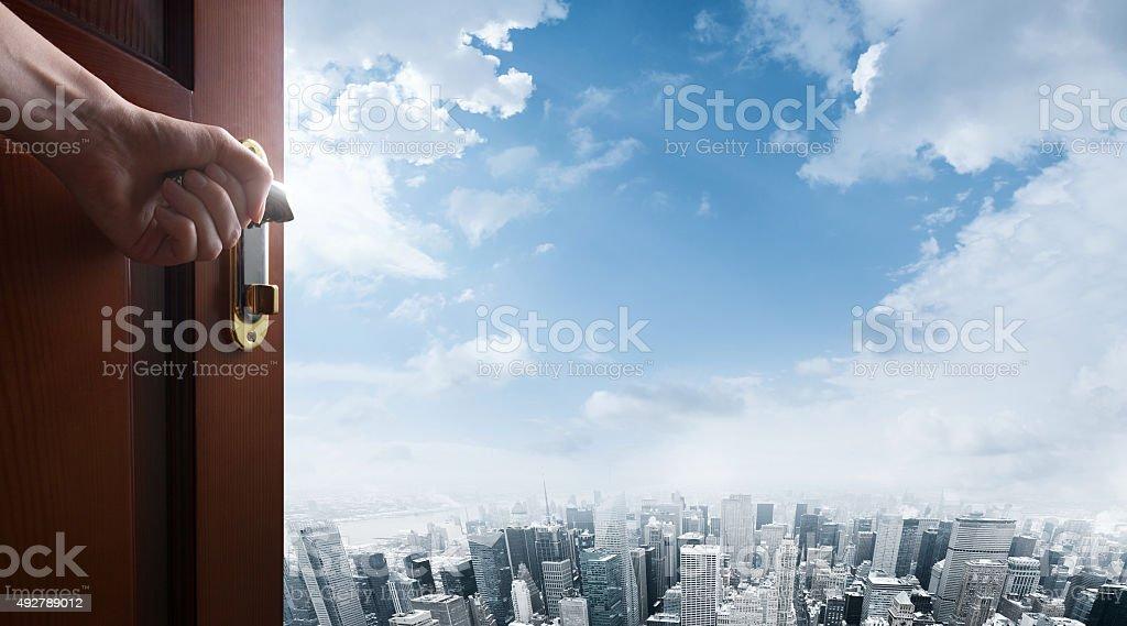 hand opens open door to city stock photo