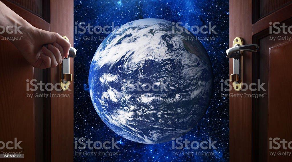 hand opens room door to galaxy stock photo