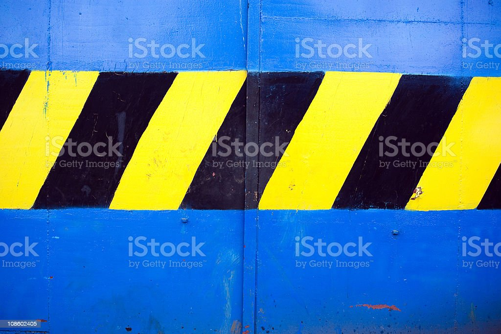 Hand painted warning stripes on blue gate royalty-free stock photo