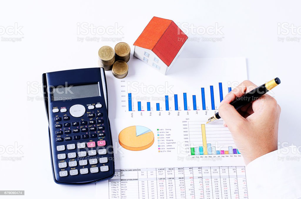 Hand people holding fountain pen on business chart and calculator with coins stack and house paper for loans concept stock photo