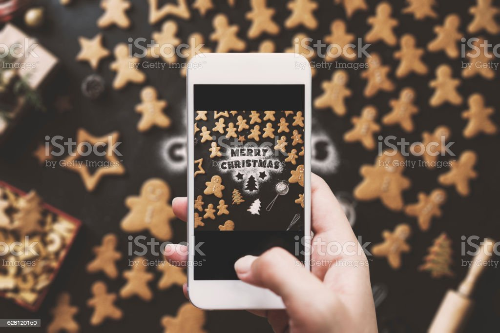 Hand photographing, Christmas gingerbread men cookies table top stock photo