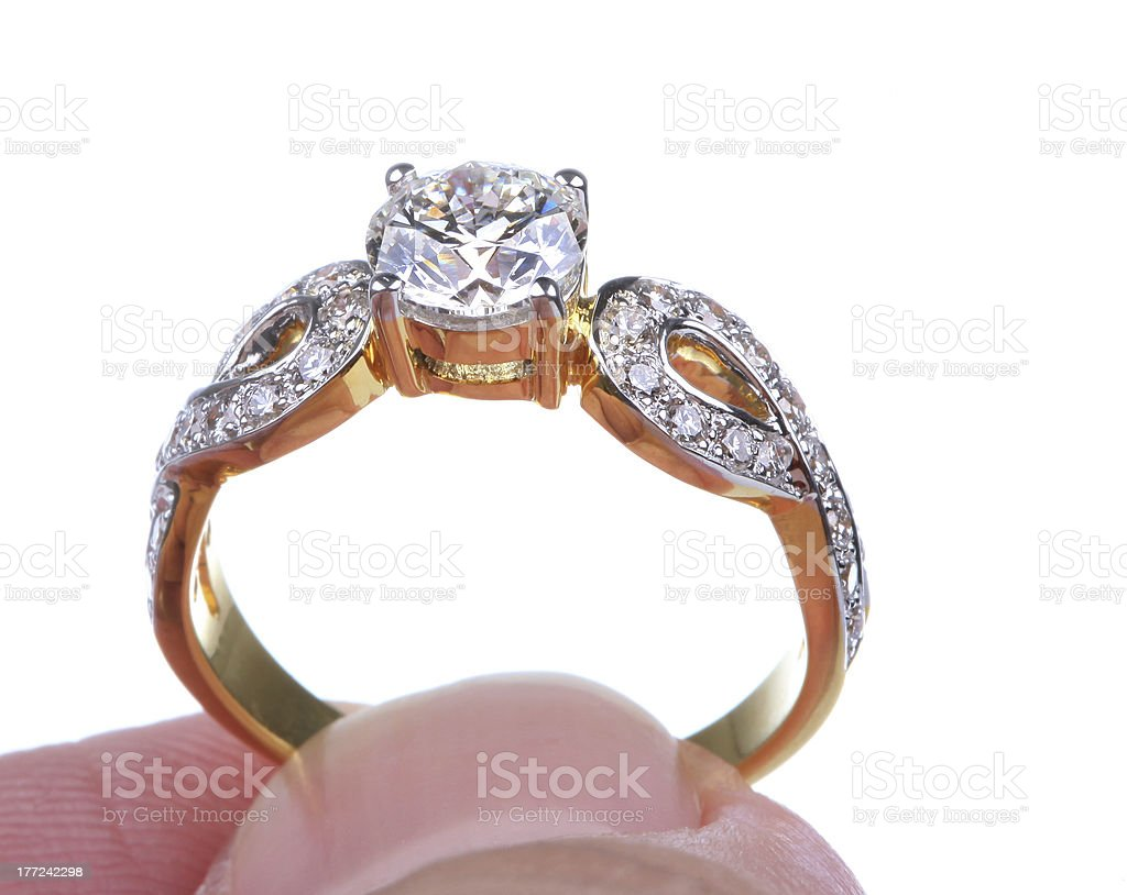 Hand pick golden ring with diamond isolated on white background. royalty-free stock photo
