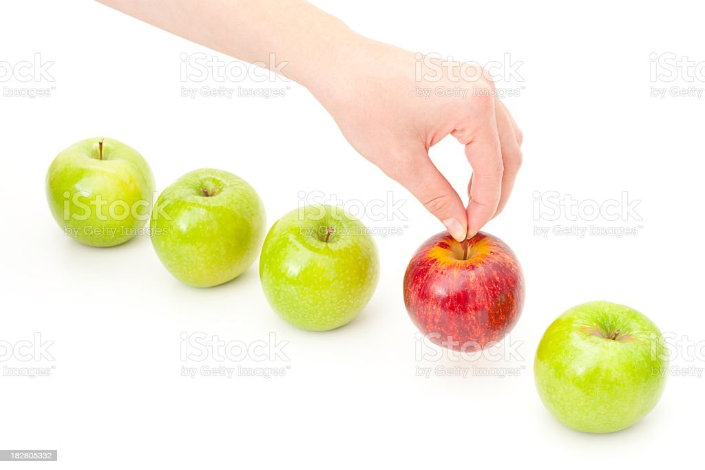 Hand Picking Apple from Row to Illustrate Choice and Decision stock photo