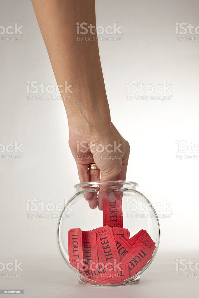 Hand Picking Ticket From Fishbowl stock photo