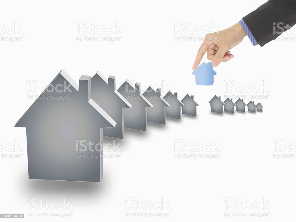 Hand picking up a small house, royalty-free stock photo