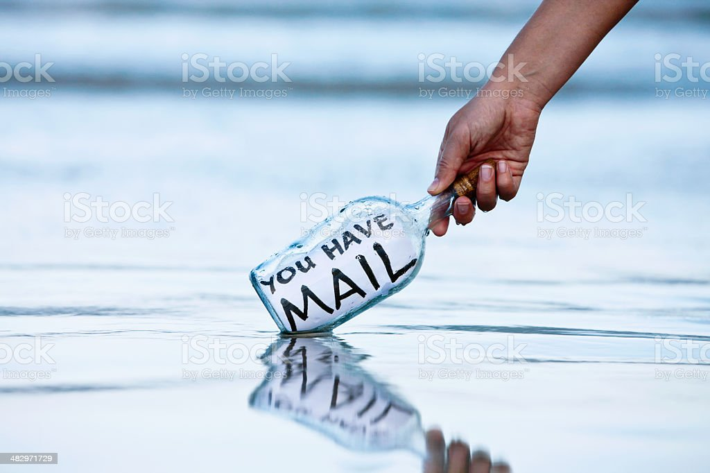 Hand picking up bottle with message: you have mail stock photo