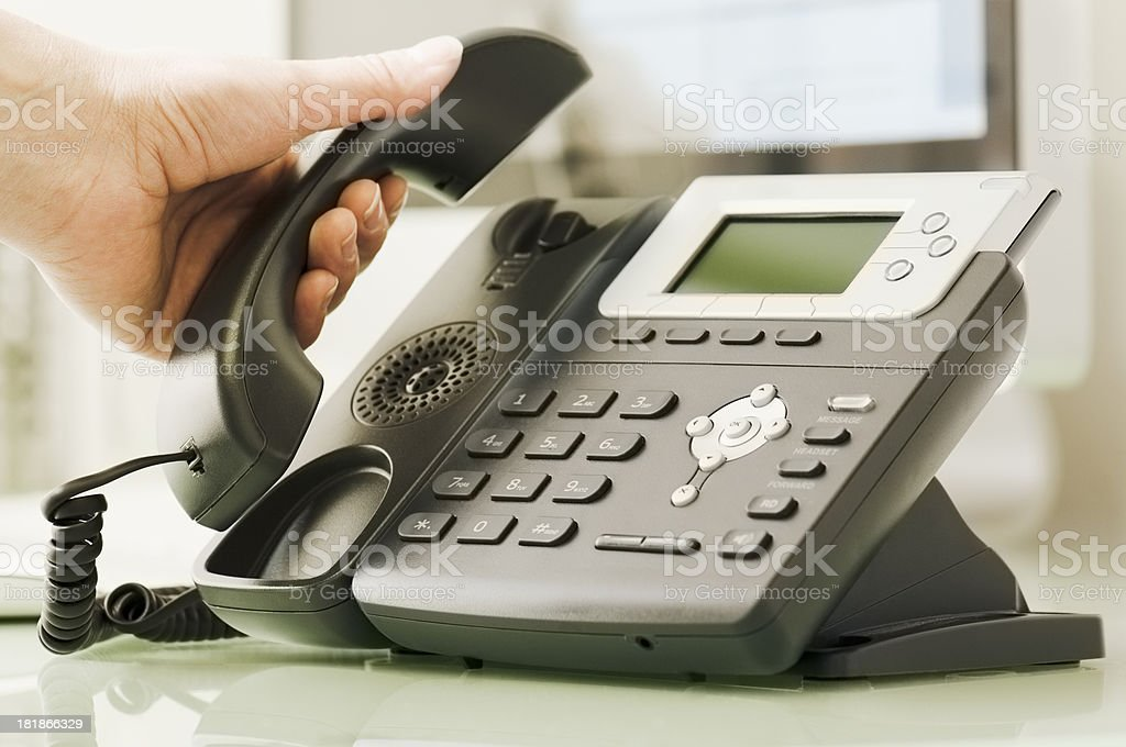 Hand picking up receiver of business telephone stock photo