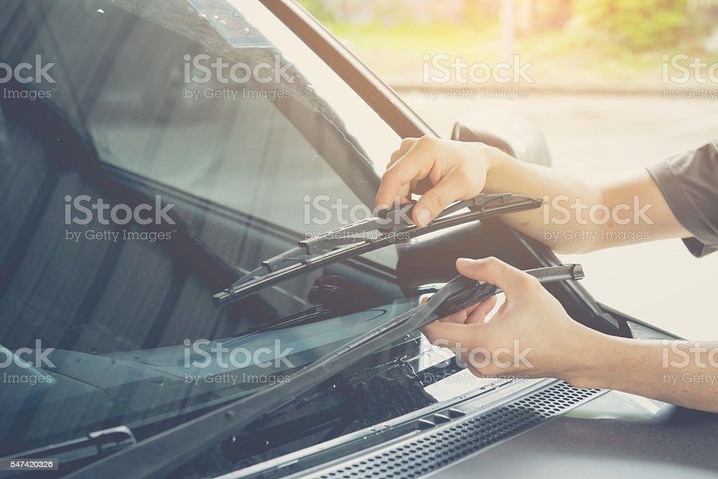 Hand picking up windscreen wiper stock photo