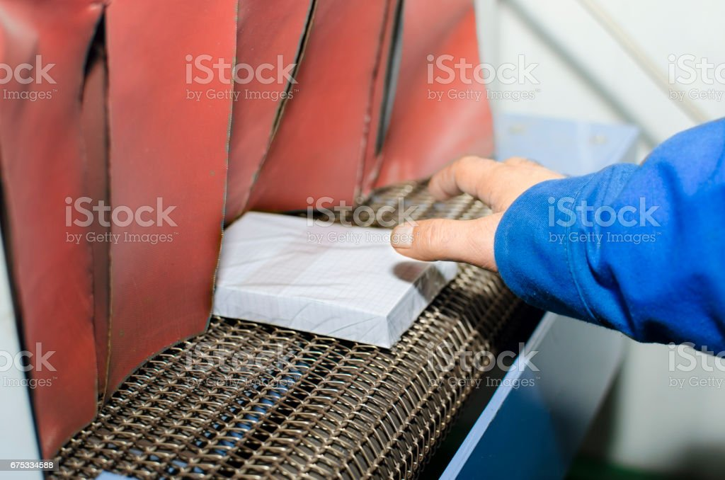 Hand place book on conveyor belt in offset print plant stock photo