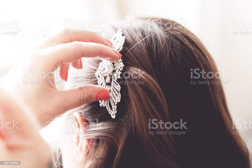 A hand placing a head piece onto a bride's hair stock photo
