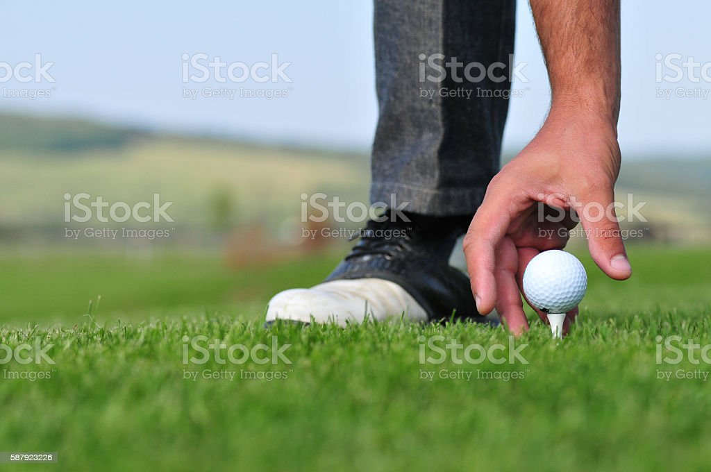 Hand placing golf ball on tee stock photo