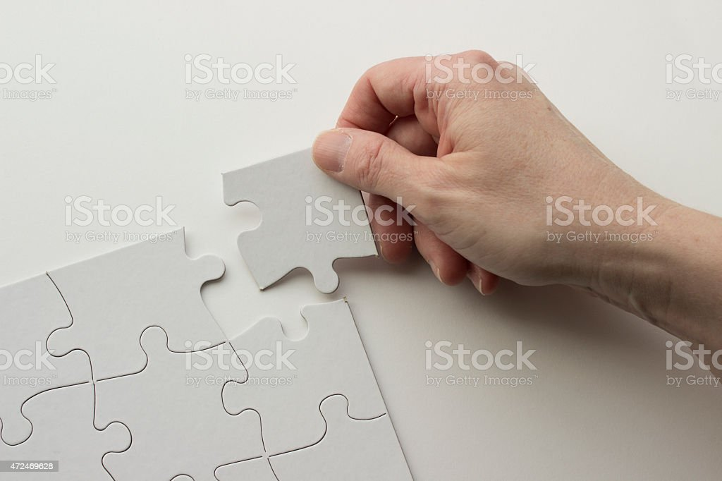 Hand Placing Puzzle Piece in Blank Puzzle stock photo