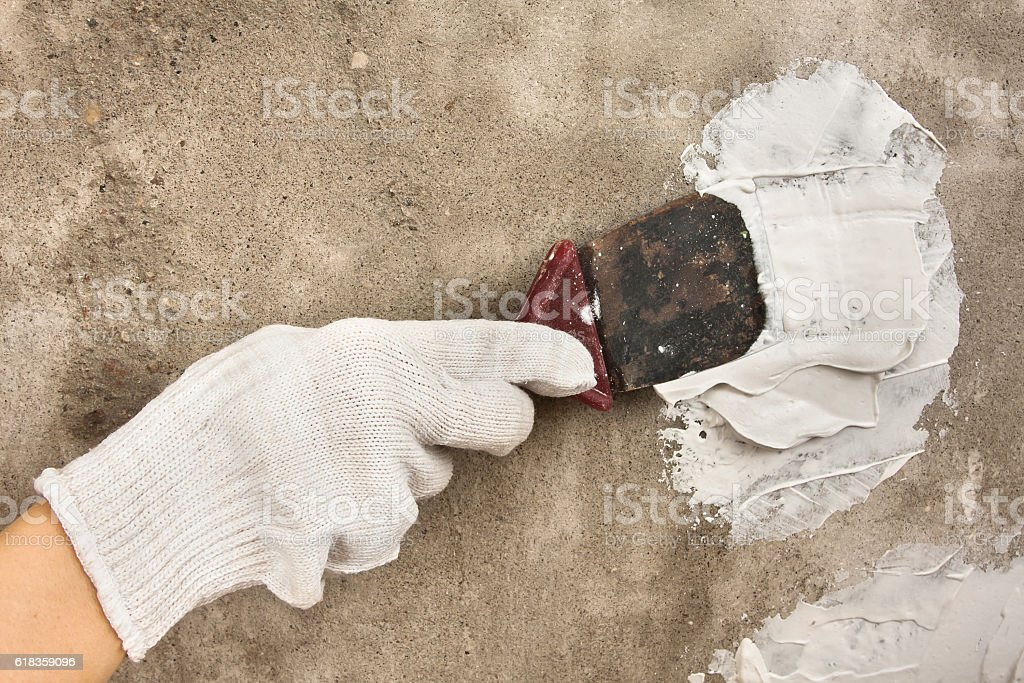 hand plastering concrete wall with spatula stock photo