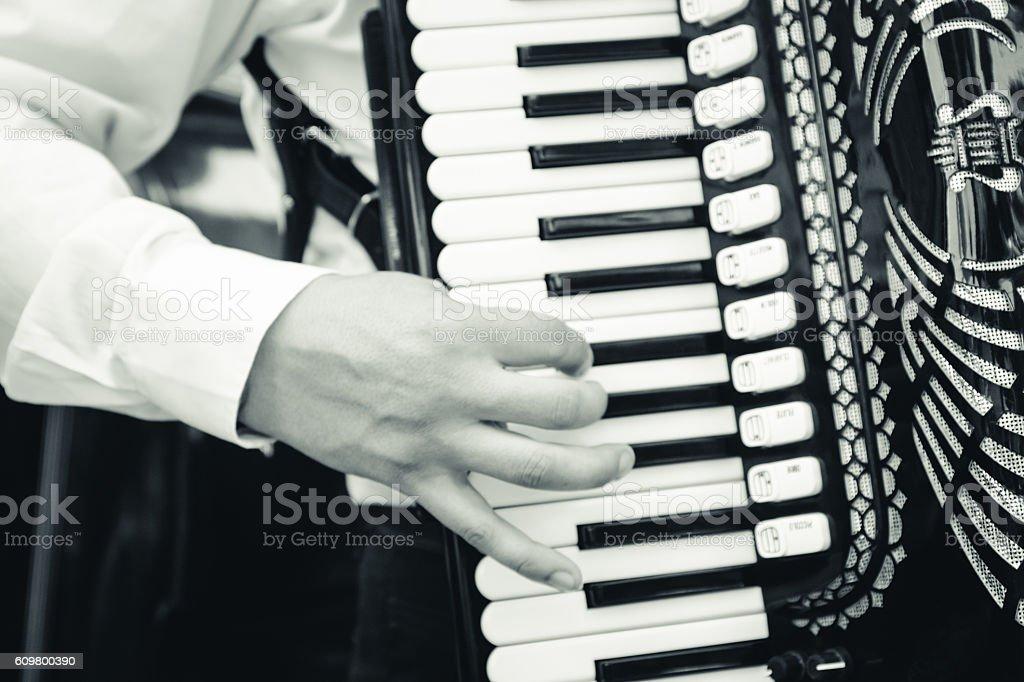 Hand playing accordion closeup stock photo