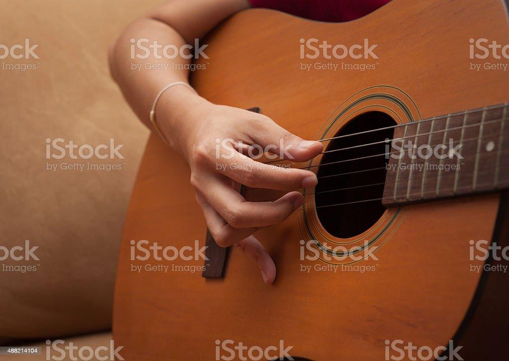 hand playing folk guitar stock photo