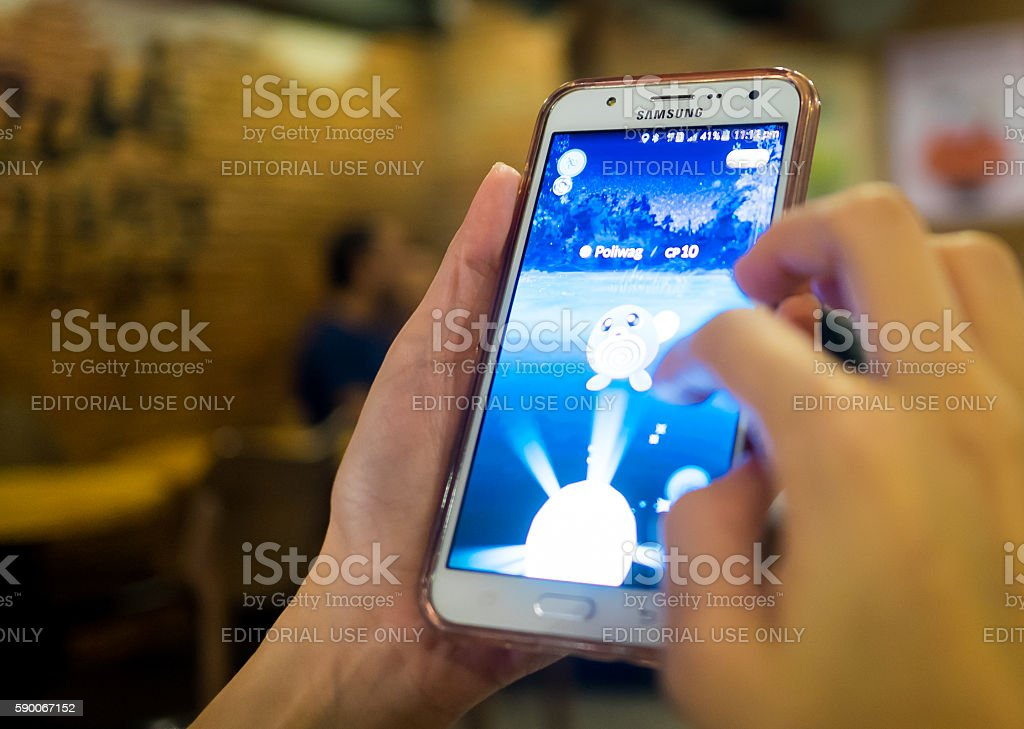 Hand playing Pokemon Go stock photo