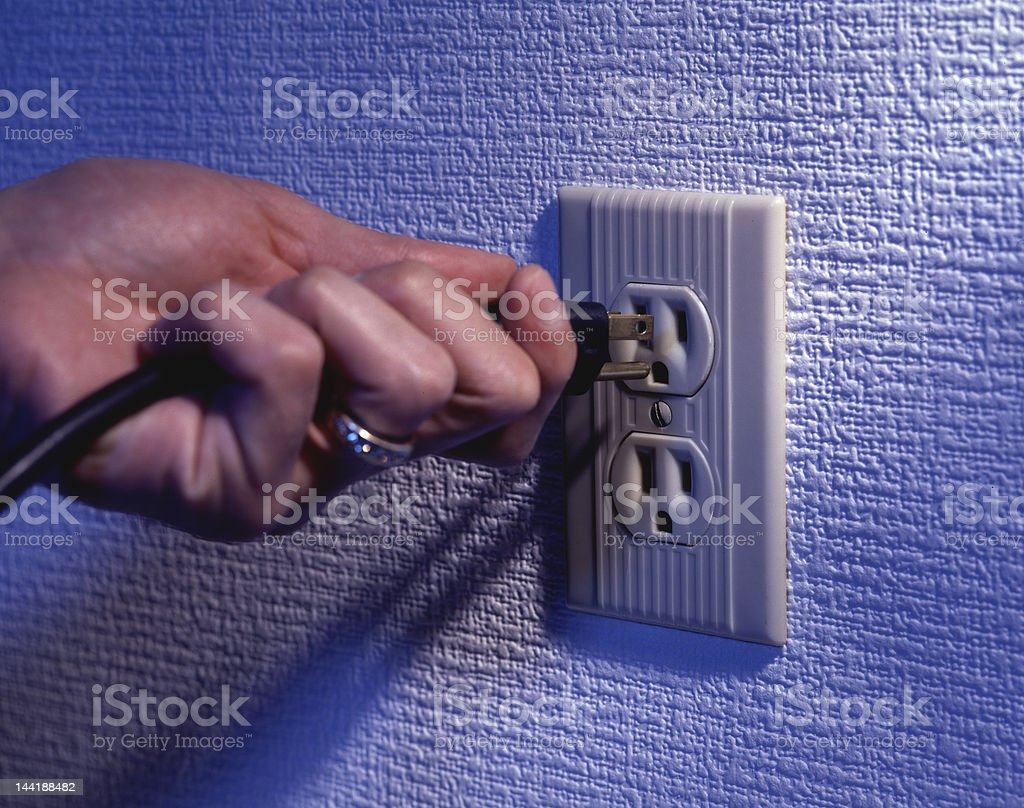 Hand plugging a power cord into socket stock photo