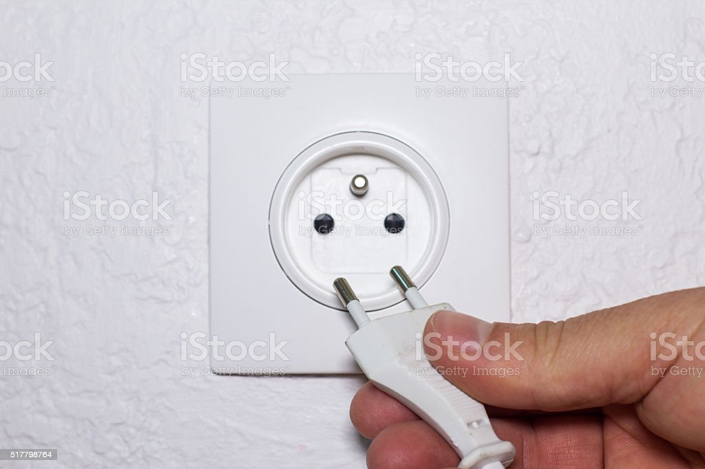 Hand plugs cord in socket stock photo