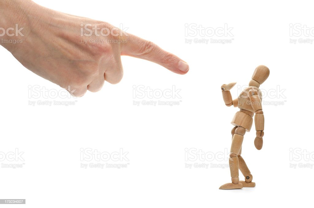 A hand pointing at a wooden mannequin stock photo