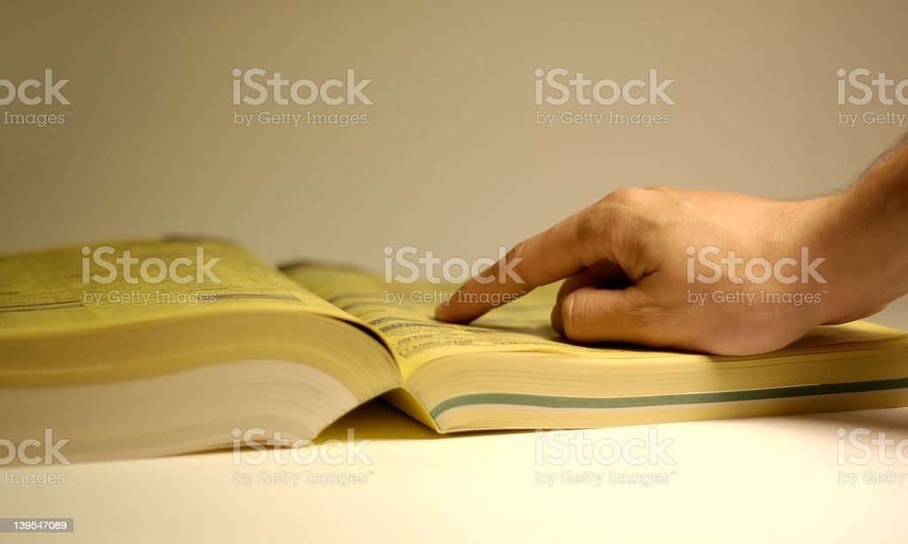Hand pointing at an ad in the Yellow Pages royalty-free stock photo