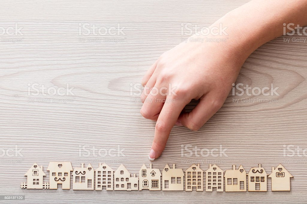 hand pointing out a house among the others mini figures stock photo