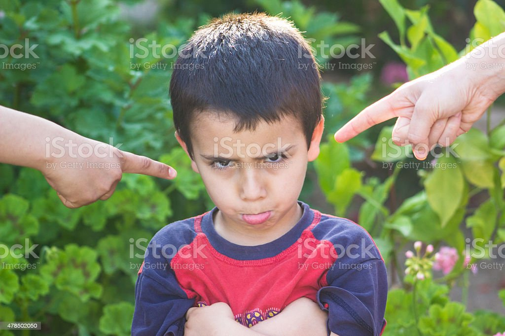 Hand pointing to guilty little boy in the garden stock photo