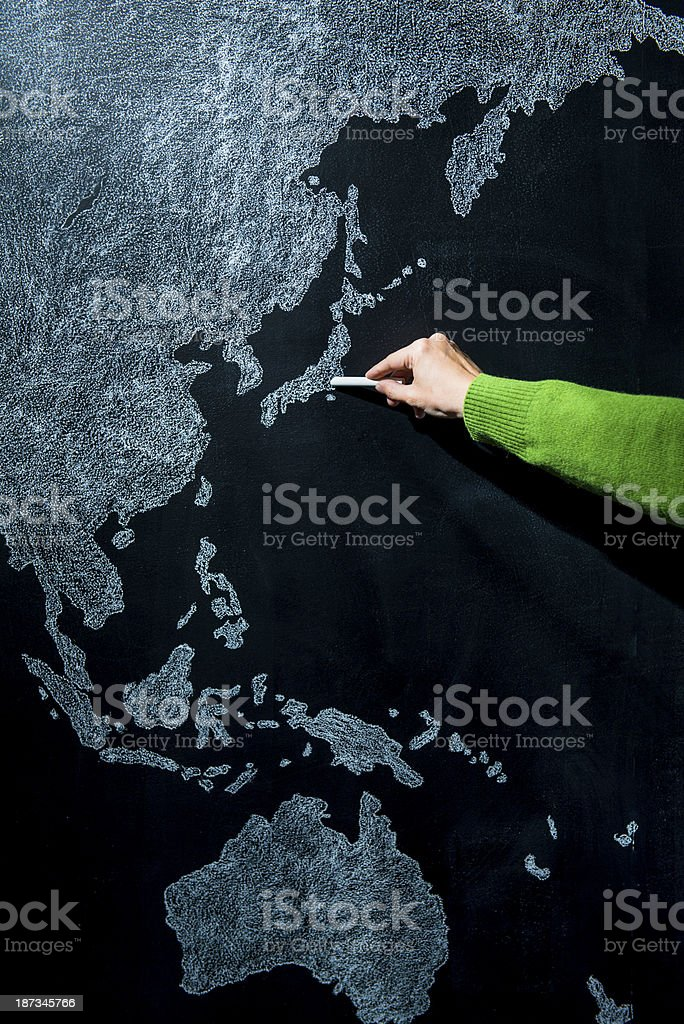 Hand pointing to Tokyo, Japan on blackboard map royalty-free stock photo