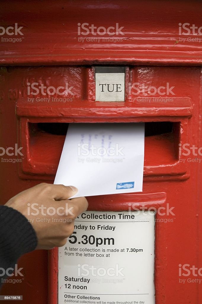 Hand posting a letter and turning it in stock photo