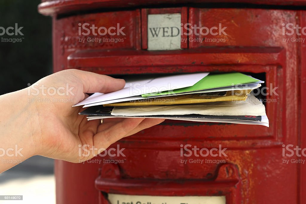 hand posting a lot of letters to red british postbox royalty-free stock photo