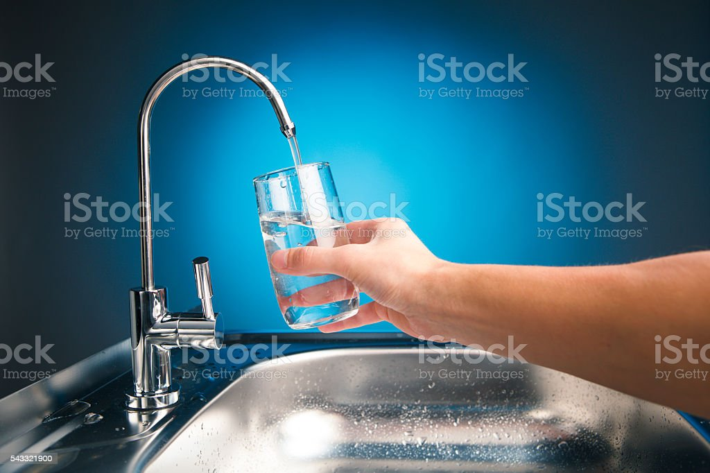 hand pouring a glass of water from filter tap stock photo
