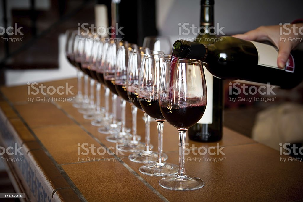 Hand pouring a row of wine glasses for tasting royalty-free stock photo