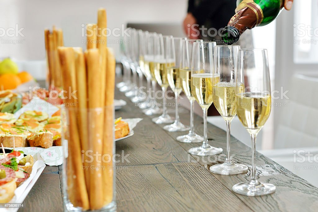 Hand pouring champagne on a party stock photo