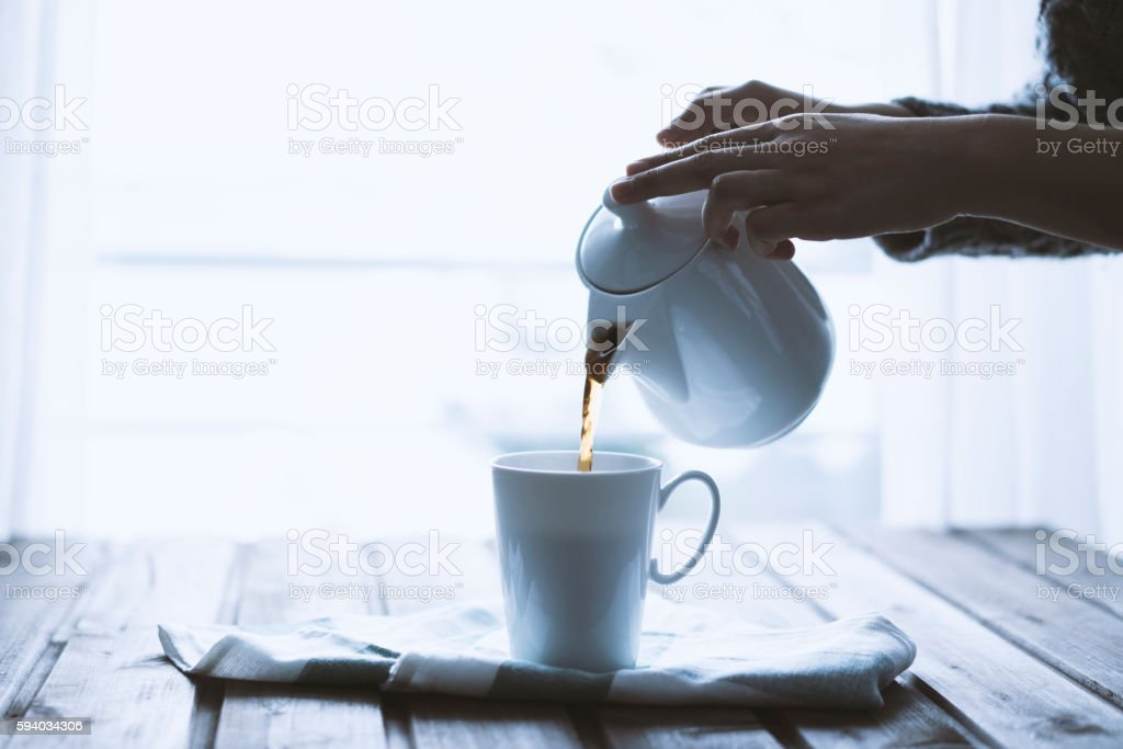 Hand pouring coffee in a mug stock photo
