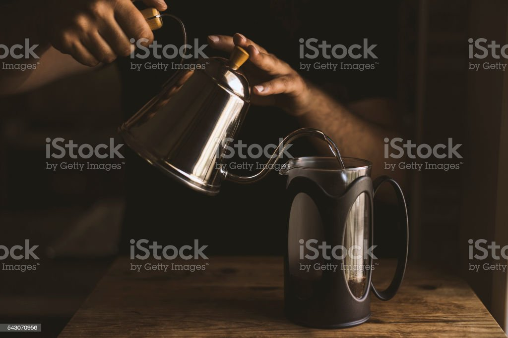 Hand pouring hot water in frech press coffee maker stock photo