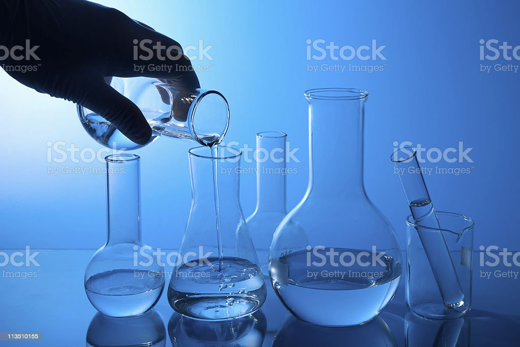hand pouring liquid into flask royalty-free stock photo