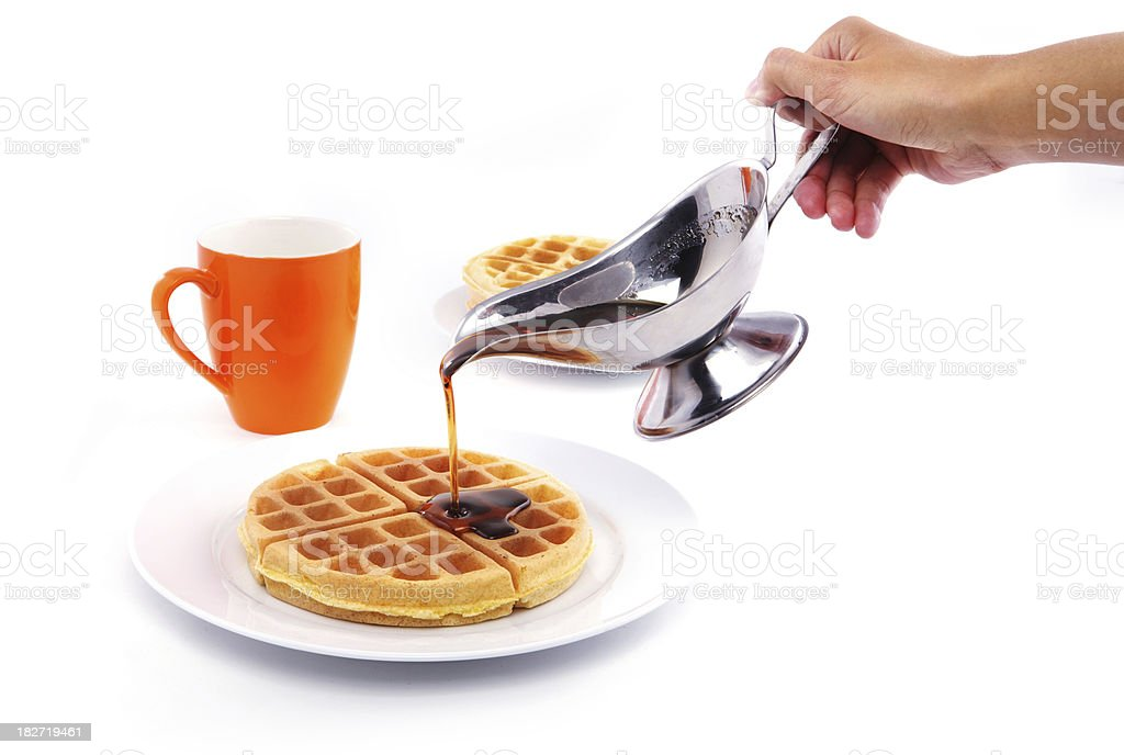 Hand pouring syrup on waffles. stock photo