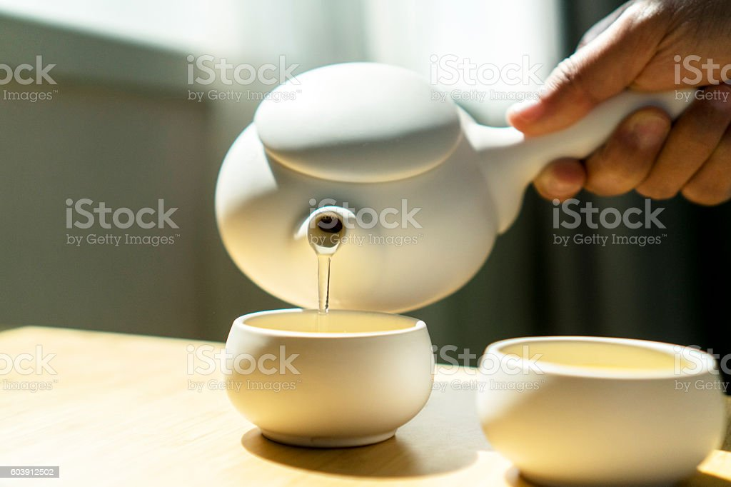hand pouring tea beside window stock photo