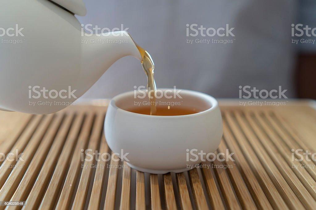 hand pouring tea beside window stock photo