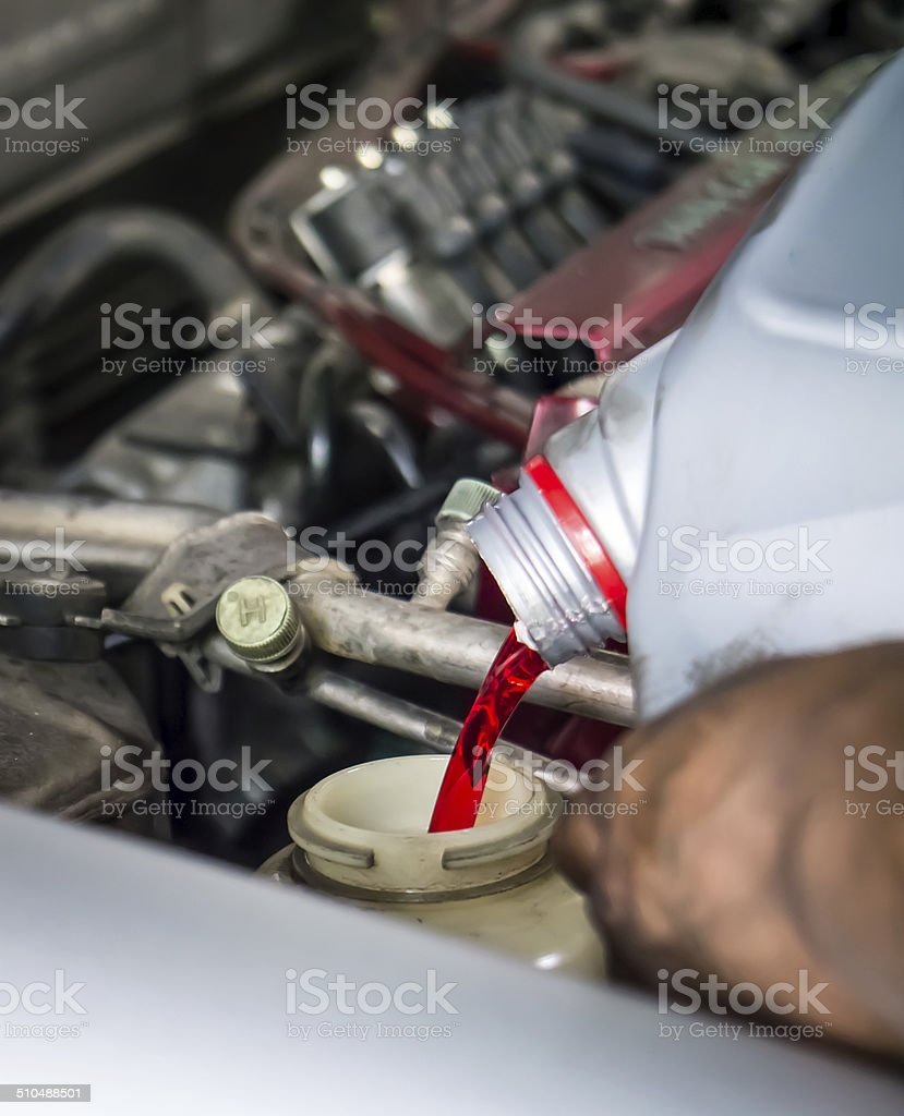 Hand pouring transmission fluid stock photo