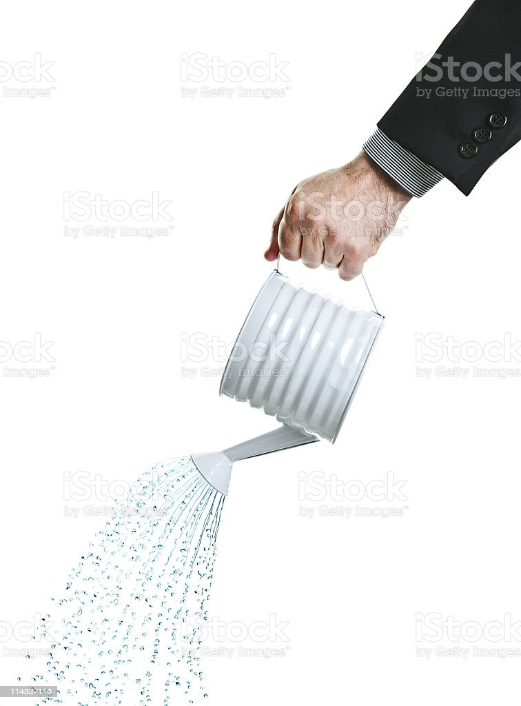 A hand pouring water from a watering can stock photo