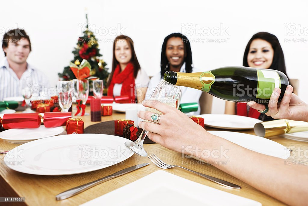 Hand pours champagne for friends celebrating at Christmas dinner royalty-free stock photo