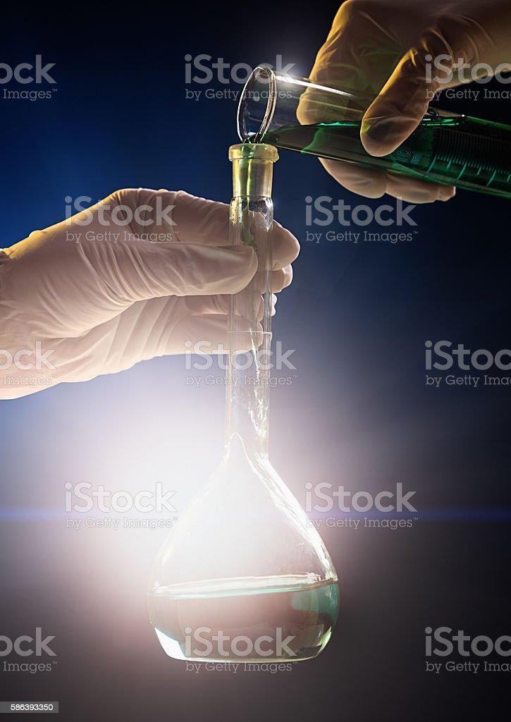 Hand pours colored liquid into spotlit laboratory flask stock photo